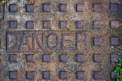 Old manhole with the word danger Stock Photos