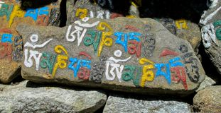 Mani Stones with Buddhist mantra in Himalaya, Nepal. Old Mani Stones inscribed with a Buddhist mantra in the Himalaya region, Nepal. Nepali color letters royalty free stock photo