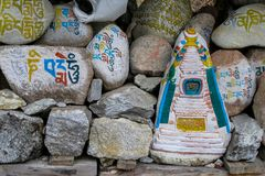 Mani Stones with Buddhist mantra in Himalaya, Nepal. Old Mani Stones inscribed with a Buddhist mantra in the Himalaya region, Nepal. Nepali color letters royalty free stock image