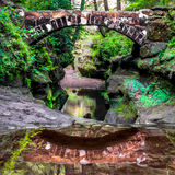 Old Mans Bridge. Reflections of the Old Mans Bridge in the water that is feeding the Devils Bathtub pool. Old Mans Cave Hocking Hills State Park, Ohio Stock Photos