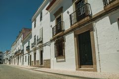 Old mansion facade with cracked white wall and wooden doors. On sunny day, in front of deserted causeway at Campo Maior. A little town with Roman, Moorish and royalty free stock photo