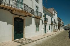 Old mansion facade with cracked white wall and wooden doors. On sunny day, in front of deserted causeway at Campo Maior. A little town with Roman, Moorish and royalty free stock image