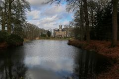 Old mansion in Netherlands with a lake view. Surrounded by trees stock photography