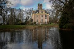 Old mansion in Netherlands with a lake view. Surrounded by trees royalty free stock photos