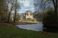 Old mansion in Netherlands with a lake view. Surrounded by trees stock photo