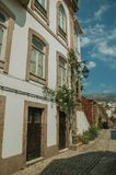 Old mansion with stone decoration in a deserted alley. Charming facade of old mansion with stone decoration and flowered shrubs in deserted alley at Covilha stock image