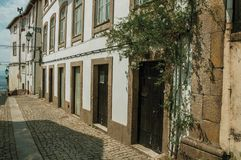 Old mansion with stone decoration in a deserted alley. Charming facade of old mansion with stone decoration and flowered shrubs in deserted alley at Covilha stock images