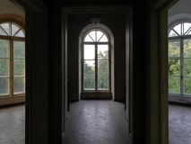 Three Mansion Rooms With Windows And Wooden Floor. Three rooms inside an old abandoned mansion with arched windows with view over trees, peeled plaster walls and Stock Photography