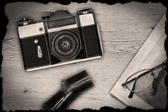 Old manual camera with newspaper and film Royalty Free Stock Photos