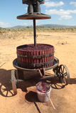 An old manual wine press. Red grape juice extraction with an old manual wine press royalty free stock photo
