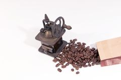 Old manual wooden coffee grinder with gear wheel and scattered coffee beans. On white background stock image