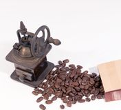 Old manual wooden coffee grinder with gear wheel and scattered coffee beans. On white background stock photos