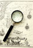 Old map - Ancient sea chart, magnifier. An antique sea sailing chart taken with a magnifying glass placed on it.  With ornate compass rose drawn on map Royalty Free Stock Photo