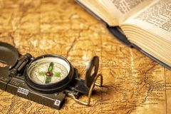 Old map with book and compass. Old expedition map with oldfashioned magnetic compass and an open book stock photography