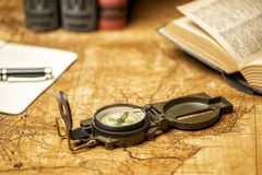 Old map with compass notebooks and books. Old expedition map with compass notebook, books and panama hat royalty free stock image