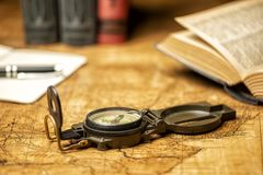 Old map with compass notebooks and books. Old expedition map with compass notebook, books and panama hat royalty free stock photography