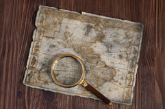 Old map and magnifying glass Stock Images