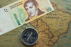 Old map of south america with argentine money and compass, close-up stock image