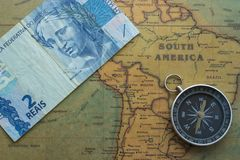 Old map of south america with brazil money and compass, close-up stock image