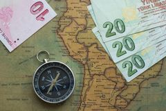 Old map of south america with money and a compass, close-up stock photography