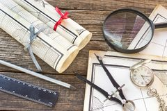 Old Maps with tools on wooden background. Old Maps with tools on a wooden background royalty free stock photography