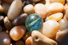 Old Marble with Pebbles. An old marble with air bubbles in the glass lays among tumbled pebbles in the sunshine Royalty Free Stock Image