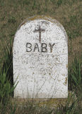 Old marble tombstone for a baby. Old, worn, and weathered marble tombstone with a cross for a baby Stock Photography