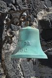 Old marine bell. On a stone wall Stock Photo