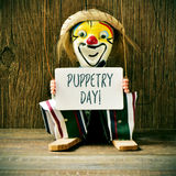 Old marionette with a signboard with the text puppetry day Stock Photos
