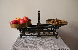 Apple scales on crochet. Old market scales for fruit and vegetables up to 5 kilo ... set of weights around 1 kilo  and 4  red apples  are almost equal ... table Stock Photo