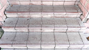 Old maroon stone steps covered with graphite with scratches and cracks Royalty Free Stock Photo