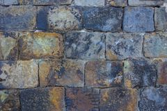 Old masonry. Homemade bricks made from wild stone. Rough uneven shape, gray, black, brown tones. The wall of a very old house. Daylight Royalty Free Stock Photography