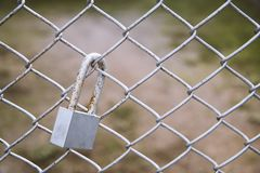 Old master key locked on metal fence with copy space. Royalty Free Stock Photography