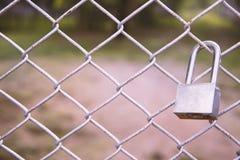 Old master key locked on metal fence Stock Images