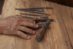 Old tool in old hand royalty free stock photography