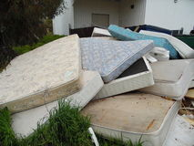 Old Mattresses Dumped. Several old mattresses, laying in a pile, dumped as refuse. Photo depicts waste, or trash, environmental irresponsibility Royalty Free Stock Photo