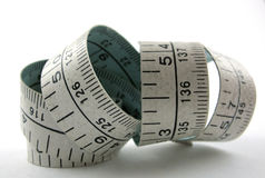 Old measuring tape. Old, worn measuring tape with centimetres and inches lies rolled on white background Stock Image