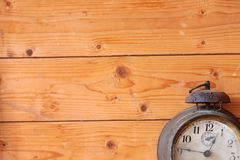 Old mechanical alarm watch background. Old vintage mechanical alarm watch on the background of wooden boards stock images