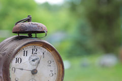 Old mechanical alarm watch. Old vintage mechanical alarm watch on the background of green foliage royalty free stock photo