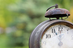 Old mechanical alarm watch. Old vintage mechanical alarm watch on the background of green foliage stock photos
