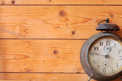 Old mechanical alarm watch. Old vintage mechanical alarm watch on the background of wooden boards royalty free stock photo