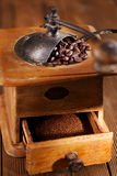 An old mechanical coffee mill. Whole and ground coffee beans from a hand coffee grinder Royalty Free Stock Photography