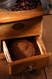 An old mechanical coffee mill. Whole and ground coffee beans from a hand coffee grinder Stock Photography