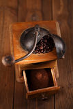 An old mechanical coffee mill. Whole and ground coffee beans from a hand coffee grinder Royalty Free Stock Images