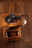 An old mechanical coffee mill. Whole and ground coffee beans from a hand coffee grinder Stock Photos