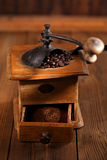 An old mechanical coffee mill. Whole and ground coffee beans from a hand wood coffee grinder Stock Photos