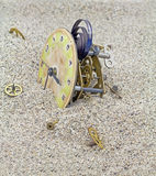 Old mechanical watch on the sand. Mechanism of old clock pinions and covered with sand stock image