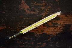 Old medical mercury thermomete on a black grunge wooden background Stock Image
