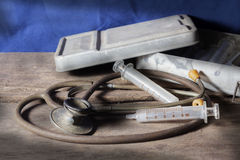 Old medical tools,syringe with stethoscope Royalty Free Stock Image