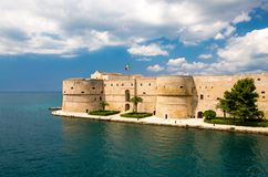 Old medieval Aragonese Castle, Taranto, Puglia, Italy. Old medieval Aragonese Castle with palm trees in front of blue sky with white clouds on sea channel in royalty free stock photography